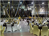 Hall decorated with brown, gold, and white chairs, tables, and streamers; piano in middle
