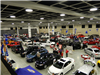 People examining a variety of cars gathered in convention hall for car show