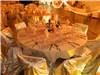 Ornate table decorations and linens in hall decorated with lights