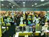Aerial view of people perusing vendor booths in convention hall trade show