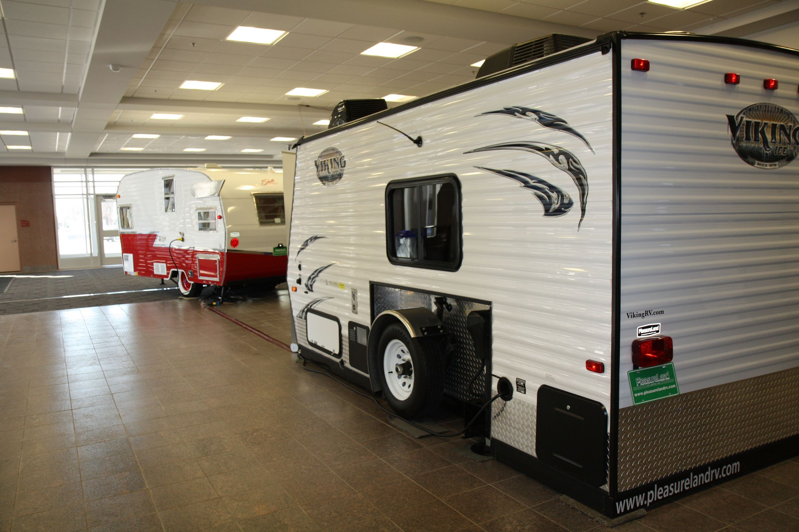 Two recreational vehicles parked in convention hall lobby