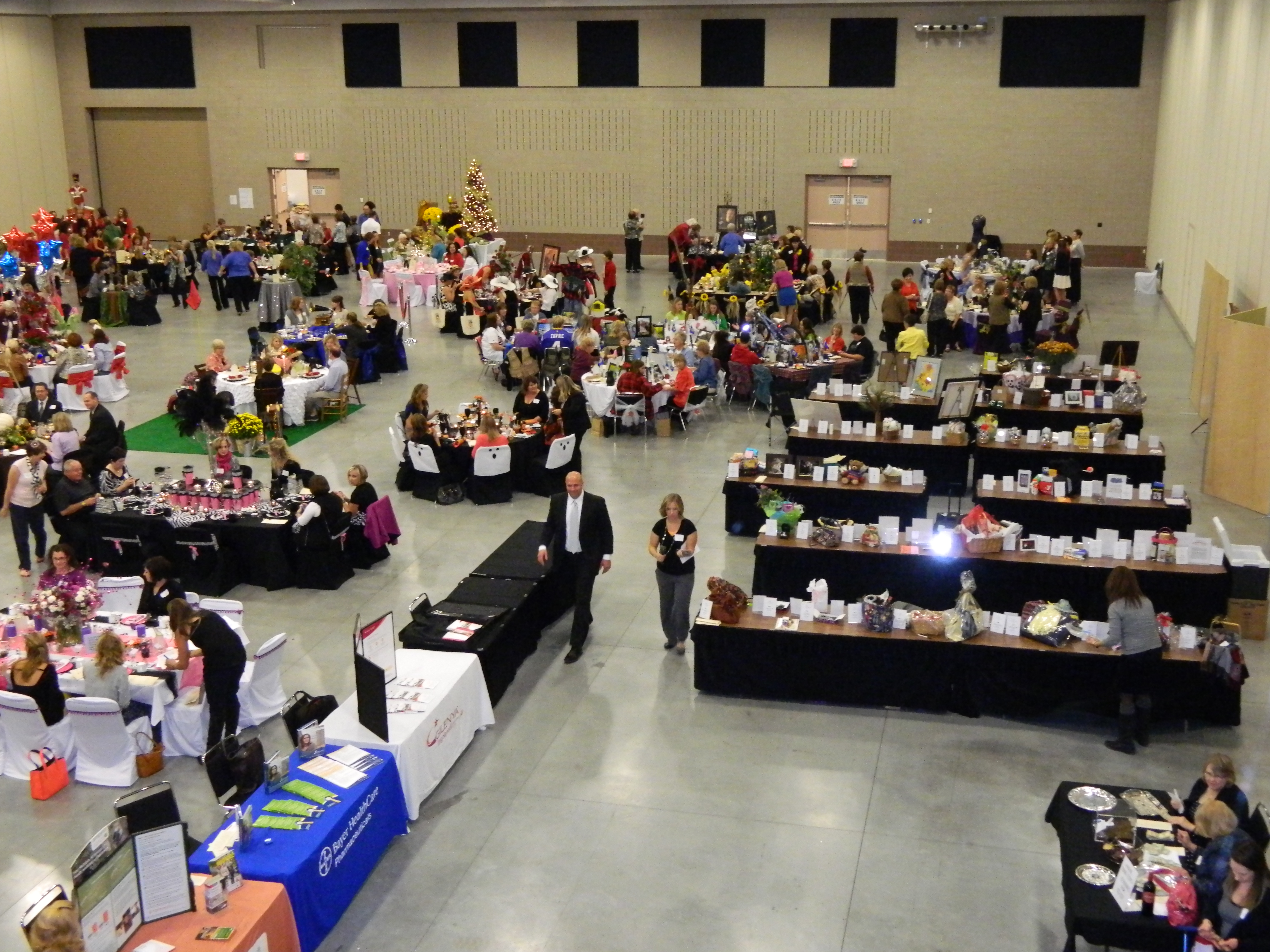 Aerial view of people dining, as well as silent auction tables in convention hall